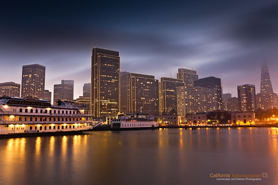 """Embarcadero - San Francisco Skyline"" Location: Embarcadero, San Francisco, California.  Embarcadero, meaning a place to embark, is an area in San Francisco with rich historic past and a very popular tourist attraction. Viewing embarcadero from the spot where I was standing literally felt how it would have been like to embark on a ship from this port. The fog often covers the city and I decided to capture some motion in the fog to further add to the feel of the image.  Tech Info: Lens: Canon 24-70mm f/2.8L @30mm Camera: Canon 5D Mk II Exposure: 30sec at f/14 and ISO 50 Filters: 2 stop SinghRay ND grad hard edge"