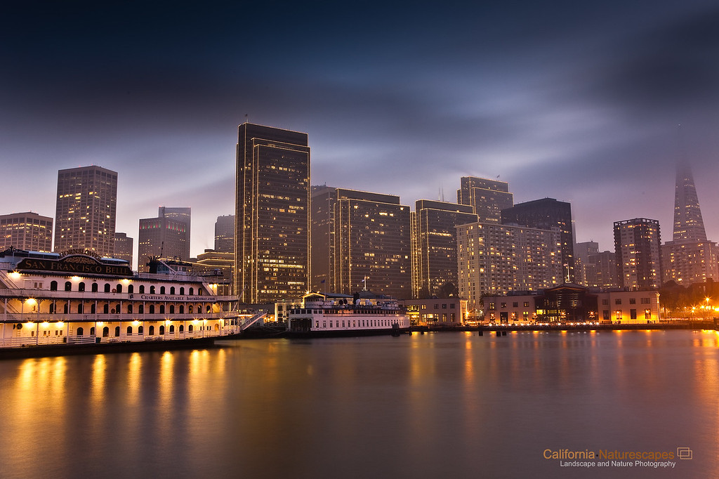 """Embarcadero - San Francisco Skyline""<br /> Location: Embarcadero, San Francisco, California.<br /> <br /> Embarcadero, meaning a place to embark, is an area in San Francisco with rich historic past and a very popular tourist attraction. Viewing embarcadero from the spot where I was standing literally felt how it would have been like to embark on a ship from this port. The fog often covers the city and I decided to capture some motion in the fog to further add to the feel of the image.<br /> <br /> Tech Info:<br /> Lens: Canon 24-70mm f/2.8L @30mm<br /> Camera: Canon 5D Mk II<br /> Exposure: 30sec at f/14 and ISO 50<br /> Filters: 2 stop SinghRay ND grad hard edge"