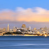"""""""Fog City - San Francisco Skyline"""" <br>Location: Fort Baker, San Francisco, California.  <p><p>The magic hour at dusk is a great time to shoot the skyline of the city. I liked the golden lights that had just switched on and were illuminating the fog layer above the city. The fog can be quite dramatic during summer months and can be seen rolling into the bay at evening. This is a very high resolution image where one can see individual windows in the buildings and can also read the text on the Fort Mason building.  <p>Tech Info: <br>Lens: Canon EF 70-200 f/4L IS @135mm <br>Camera: Canon 5D Mk II <br>Exposure: 30sec at f/9 and ISO 100 <br>Filters: SinghRay 2 stop hard edge ND grad  <p>The waterfront area at Fort Baker is a great place to shoot not just the skyline but also the Golden Gate bridge. I had originally planned on shooting the bridge which is just to the right but light was better looking towards the skyline. And if you are in mood for crab you can also catch some here."""