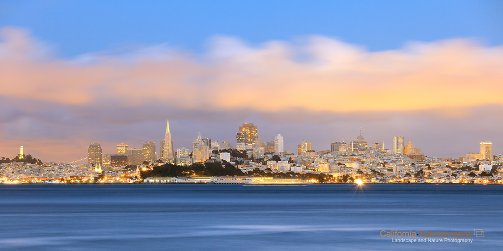 """Fog City - San Francisco Skyline"" <br>Location: Fort Baker, San Francisco, California.  <p><p>The magic hour at dusk is a great time to shoot the skyline of the city. I liked the golden lights that had just switched on and were illuminating the fog layer above the city. The fog can be quite dramatic during summer months and can be seen rolling into the bay at evening. This is a very high resolution image where one can see individual windows in the buildings and can also read the text on the Fort Mason building.  <p>Tech Info: <br>Lens: Canon EF 70-200 f/4L IS @135mm <br>Camera: Canon 5D Mk II <br>Exposure: 30sec at f/9 and ISO 100 <br>Filters: SinghRay 2 stop hard edge ND grad  <p>The waterfront area at Fort Baker is a great place to shoot not just the skyline but also the Golden Gate bridge. I had originally planned on shooting the bridge which is just to the right but light was better looking towards the skyline. And if you are in mood for crab you can also catch some here."