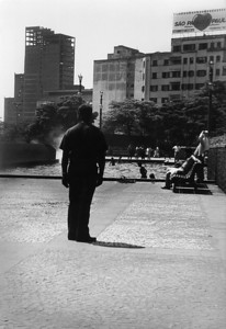 """Absent Bystander """"Praça da Sé"""" is the heart of São Paulo megalopolis. In a hot day of summer, a bystander directs his look to nothing while homeless children get some refreshment in the public fountain."""