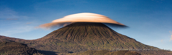A lenticular cloud hangs in the still morning air over Karisimbi, Volcanoes National Park in Rwanda. Straddling The Congo border these mountains are the home to some of our closest ancestors and the almost extinct, always majestic Mountain Gorillas.  Photo is a High Dynamic Range photo using +/-2 EV and processed using Photomatix Pro and Lightroom 2  When ordering prints select 'panoramic' size options