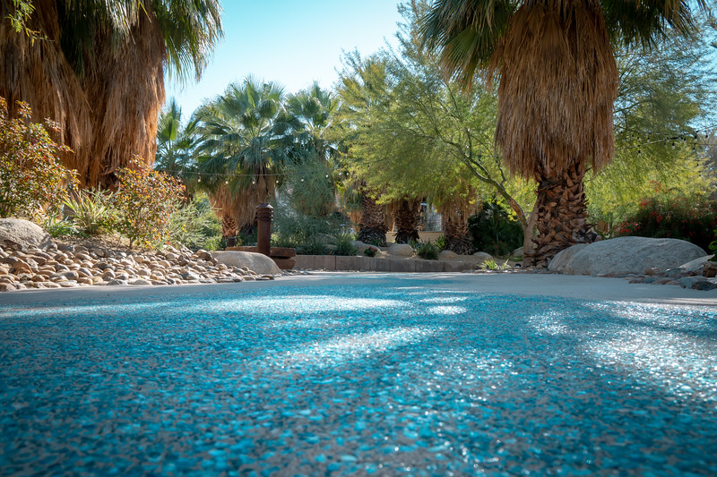 The pathway paved with blue stones or glass to resemble a river.