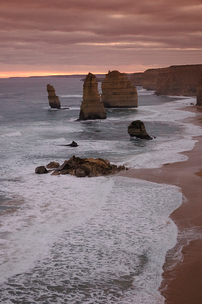 An image shot in the evening's setting sun of The Twelve Apostles, Victoria, Australia. The Twelve Apostles are located along the spectacular Great Ocean Road. They were originally named the 'Sow and Piglets'. The Twelve Apostles were formed by erosion of the original coastline. The constant action of the sea on the limestone slowly wore down the rocky cliff, gradually leaving individual rocks.