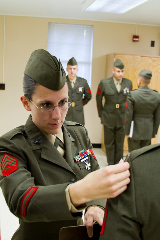 Sergeant Areca Kroll inspects the uniform of a fellow Marine at Sergeant's Course 1-11 in Camp Johnson, North Carolina.  The uniform inspection exam was one of many evaluations conducted at this professional military education school, including close-order drill, patrol operations, weapons maintenance, and public speaking.