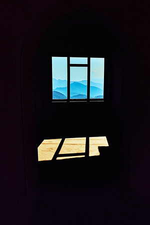 Blue mountain framed by large window and door arched in contrasty indoor