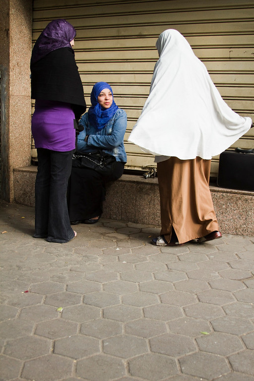 Three Egyptian women gather on a street corner, chatting.