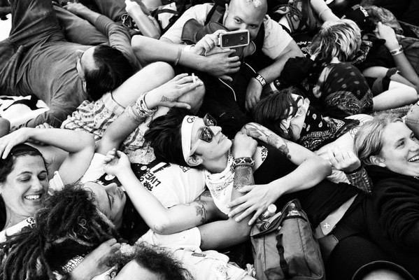 """Black bloc protesters form a """"human quilt"""" in Centennial Park, Ybor City district, Tampa, Florida.  The quilt is a method of """"sit-in"""" protesting, but in this instance, the protesters were taking a moment to relax. August 28th, 2012."""