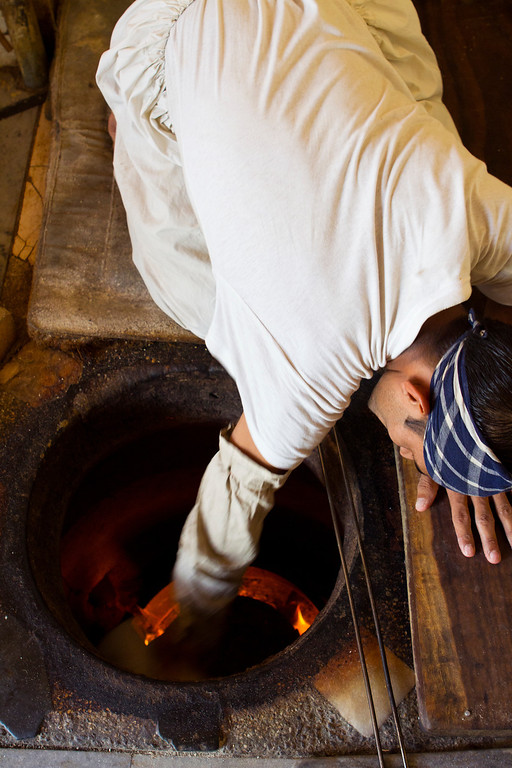 A man bakes naan in this subterranean oven in Islamabad, Pakistan.