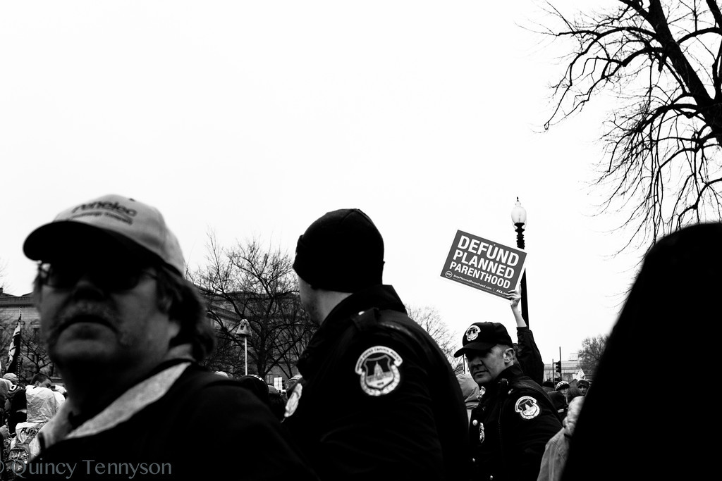 A protester at the March for Life 2012 lifts their sign high above the crowd as the march makes its way to the front of the Senate building.