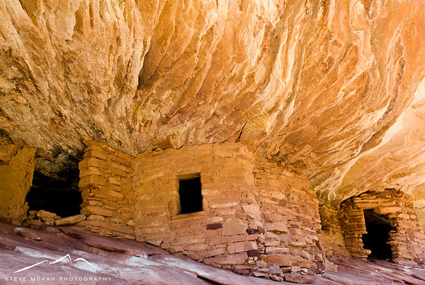 After leaving Monument Valley and on the way to Moab, we stopped in the middle of nowhere (no, really) and hiked down a dry river bed to find the House on Fire.  This is an old Anasazi ruin that's preserved under the side of a cliff.  When the sun reflects off the sandstone below (meaning you have to be there at the right time!), the rock formations above make it look like it's on fire.