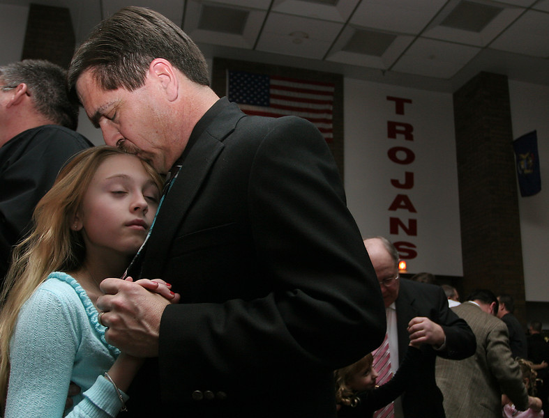 Evening News photo by MARVIN HALELAMIEN<br /> Tom Hawley rests his head against his daughter, Kayla's, 12, during the 20th annual Daddy-daughter dance at Monroe High School Saturday night. He bought her a dozen roses and said they have attended annually for about eight years.