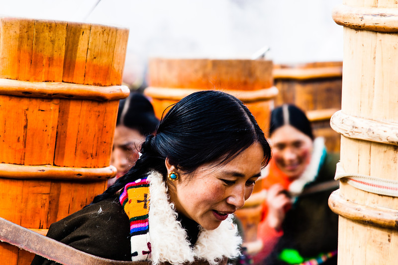 The Tibetan women carry the butter tea in huge water barrels slung on their backs.