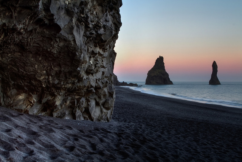 <H3>Midnight Stroll on a black sand beach </H3> Weird and wonderful rock formations occur when volcanic activity meets ocean.You can see part of a cave with crystallized basalt walls and the famous sea stacks - Reynisdrangur in the distance. The beach is Reynisfjara close to the town of Vik