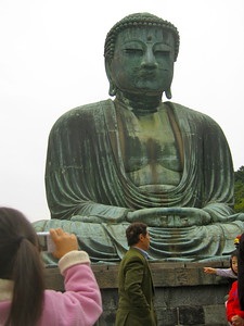 A little girl takes a cellphone picture of the Great Buddha of Kamakura.