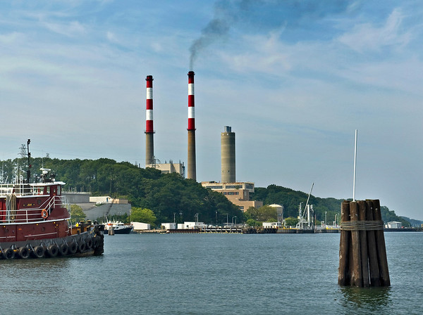 The power plant stacks in Port Jefferson harbor, with tugboat at the pier