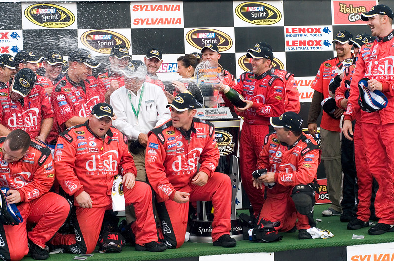 The Dish Network team celebrates with a shower of Champagne after wining the Sylvania 300