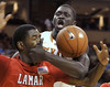 Texas forward Alexis Wangmene, rear, comes into close contact with Lamar forward Vincenzo Nelson while fighting for a loose ball during the first half of an NCAA college basketball game in Austin, Texas, Wednesday, Dec. 1, 2010.