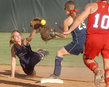 Leake Academy shortstop Leslie Morgan (left) flips the ball to teammate Brittany Gross just ahead of Jackson Prep's Kelly Chandler during Saturday's MPSA state championship game at Mississippi College in Clinton.  Chandler was safe at second on the play when Gross was unable to glove the ball cleanly.