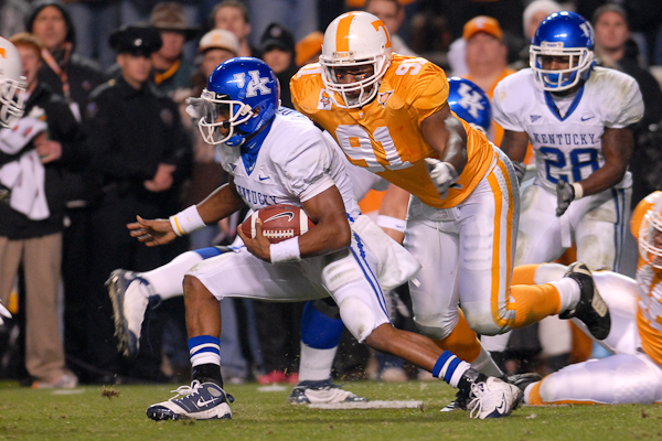 UK quarterback Randall Cobb is pursued by UT defensive end Robert Ayers in Saturday night's game at Neyland Stadium.  Photo by Bryan Lynn.