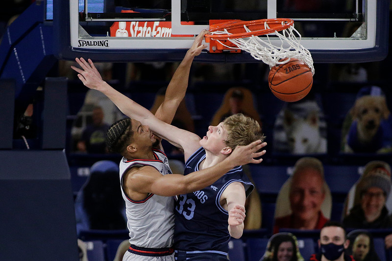 Gonzaga guard Aaron Cook, left, dunks over San Diego forward Ben Pyle during the second half of an NCAA college basketball game in Spokane, Wash., Saturday, Feb. 20, 2021. Gonzaga won 106-69. (AP Photo/Young Kwak)