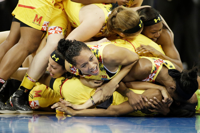 Maryland's Aja Ellison, center, and her teammates celebrate after winning a women's college basketball regional final game against Tennessee in the NCAA tournament, Monday, March 30, 2015, in Spokane, Wash. Maryland won 58-48. (AP Photo/Young Kwak)
