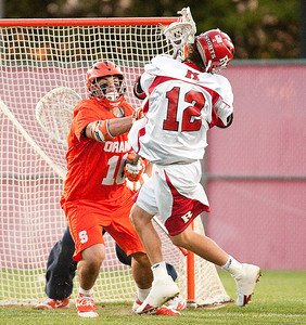 Rutgers' Tad Stanwick #12 takes a stick from Syracuse goalie John Galloway #15 during NCAA Lacrosse action between Rutgers Scarlet Knights and the #2 Syracuse Orange at Yurcak Field in Piscataway, New Jersey.