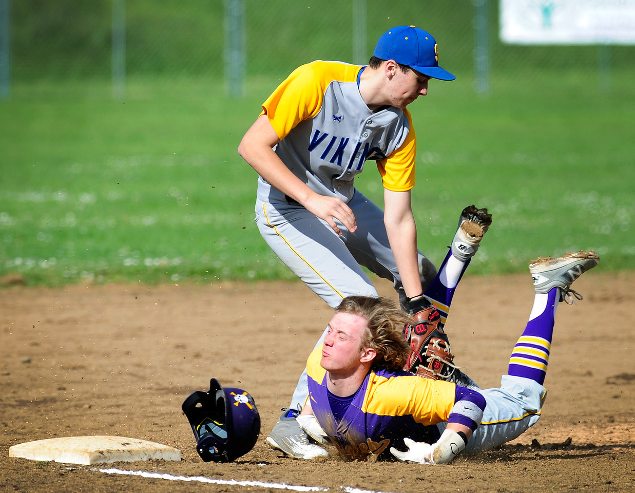 Siuslaw's Caleb Hennessee (2) tags Marshfield's Braden Denton (1) for an out as he slides into third base during the first game of the double header home opener against Siuslaw. The Pirates defeated the Vikings, 9-5.