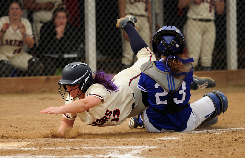 Lakers' Shelby Harris (13) dives towards home plate as Clark's Sarah Hoechlin (23) catches the ball during the first game of a double header at home on Tuesday. Hoechlin was called for obstruction. The Lady Lakers defeated Clark, 12-4, in a run rule victory.