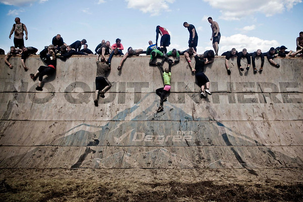 Participants climb a sloped wall that in the 2012 Tough Mudder at Mt. Snow in West Dover, VT on May 5, 2012.