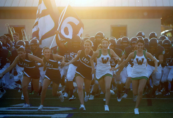 Cheerleaders lead the Little Rock Christian football team onto the field before their game against Shiloh Christian Friday, September 9, 2016