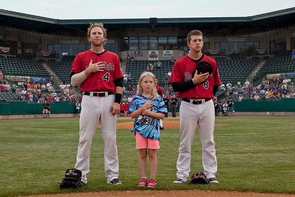 Kate Connery, 8, of Newington stands between Rock Cat's second baseman, Brad Boyer, left and A..J. Pettersen, short-shop, right as the national anthem was played before the game on Tuesday, June 3, 2014.