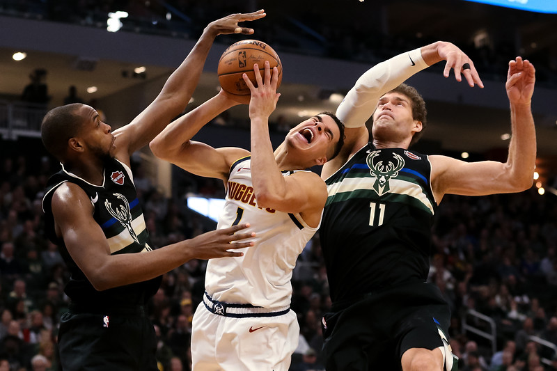 Michael Porter Jr. #1 of the Denver Nuggets attempts a shot while being guarded by Khris Middleton #22 and Brook Lopez #11 of the Milwaukee Bucks in the third quarter at the Fiserv Forum on January 31, 2020 in Milwaukee, Wisconsin.