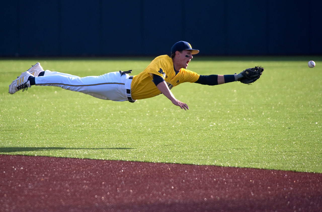 CAPTION INFORMATION University of Michigan's Eric Jacobson dives but can't reach the ball and Central Michigan scores a run in the first inning at Ray Fisher Stadium in Ann Arbor on April 2, 2014.  The field is all synthetic except for a dirt pitchers mound.  (Mark Bialek / Special to the Det News)