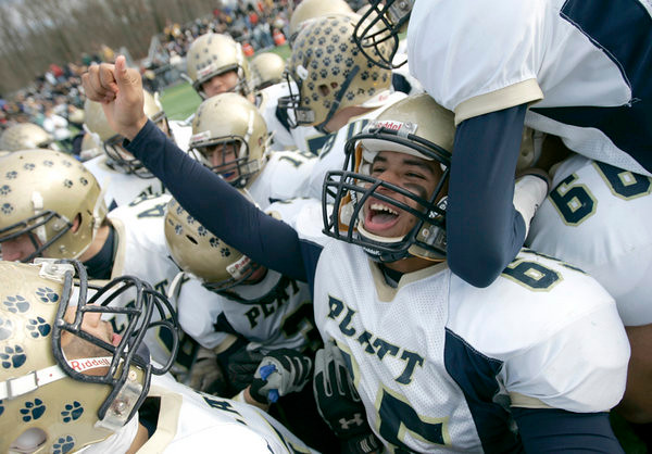 Juan Vasquez, a Platt High School football player shouts in the huddle begining the second half of the Stoddard Bowl at Falcon Field in Meriden on Thanksgiving Day. Platt High School won against Maloney High School, 20-18.
