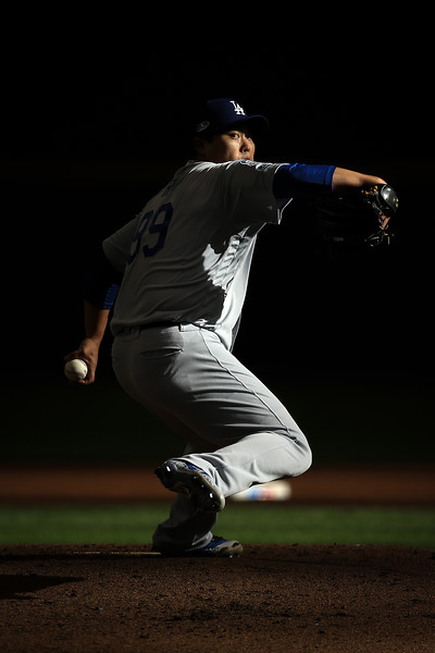 Hyun-Jin Ryu #99 of the Los Angeles Dodgers throws a pitch against the Milwaukee Brewers during the first inning in Game Two of the National League Championship Series at Miller Park on October 13, 2018 in Milwaukee, Wisconsin.