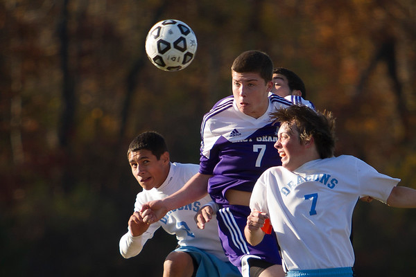 East Granby's Nicholas Fersch, center, heads the ball past the MLC goal keeper dispite the efforts of Andrew Wyse, right, and Matthew Rios, left. The new CREC Metropolitan Learning Center hosted the first round Class S Boys Soccer Tournament game.