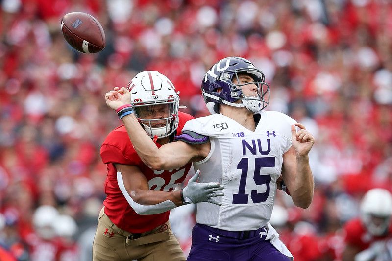 Eric Burrell #25 of the Wisconsin Badgers forces a fumble against Hunter Johnson #15 of the Northwestern Wildcats in the third quarter at Camp Randall Stadium on September 28, 2019 in Madison, Wisconsin.