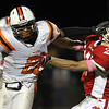 Beverly junior running back Isiah White, left, throws a stiff arm to the facemask of Masconomet senior defensive back Adam Murphy on a long 4th quarter run on Friday evening. White and senior captain Brendan Flaherty led the way for the Panthers as they defeated the Chieftans 30-14. David Le/Staff Photo