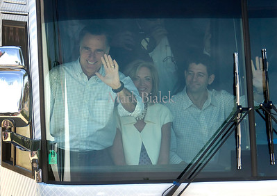 Ann and Mitt Romney and Paul Ryan wave to the crowd as they arrive for a campaign stop in Commerce Township, MI on August 24, 2012.