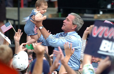 9/13/04 -  President Bush hoists a baby while interacting with the crowd after giving a campaign speech in Bailey Park in Battle Creek Monday.  (Mark Bialek / Special to the Gazette)