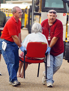Two men carry an elderly woman to a waiting JATRAN bus as she and other storm evacuees are moved from the United Penticostal Church International Regional Office and Camp on Mississippi 18 to the Mississippi Trademart on Wednesday. The group of over 100 resdients and staff from the Meadow Crest Living Center in Gretna, La had been housed at the camp since fleeing from Hurricane Katrina on Sunday and had been without power there since Monday. Soaring temperatues took their toll on the group, claiming the life of one person and leaving several others in poor conditon. Several of the most severe cases were transported by ambulance to area hospitals while the remainder were transported to the Trademart.