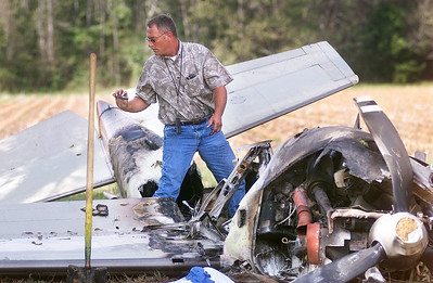 FAA inspector Ed Aycock finds a cell phone while sifting through the wreckage of a Cessna 210 aircraft that crashed into a cotton field Wednesday morning near the John Bell Williams Airport north of Raymond. The plane came to a rest upside-down then caught fire. The pilot was able to walk away from the wreckage.