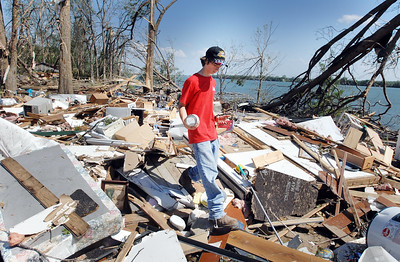 Logan Beard, 13, helps sift through the debris of Ronnie Tyler's home on Eagle Lake in Warren County north of Vicksburg that was one of several in the area completely destroyed when a tornado swept along the lake's north shore Saturday morning.