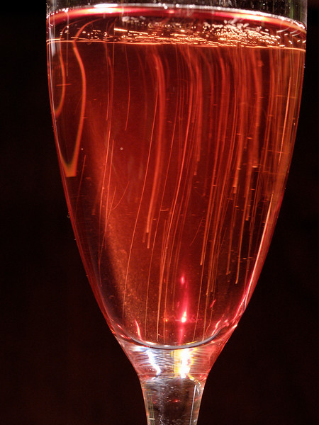 Bubbles rise to the surface in a glass of raspberry champagne.