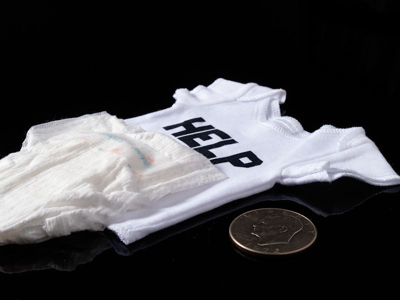 Pemature baby shirt and diaper with a coin to demonstrate the scale.