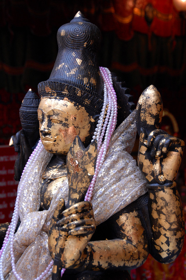 Gold leaf stuck on religious statues. Image shot in Bangkok, Thailand.
