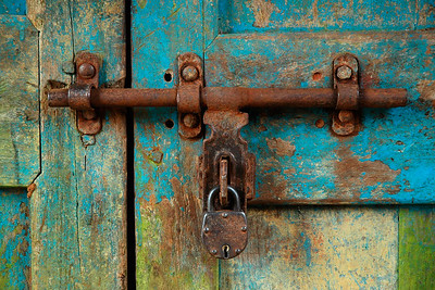 Lock As we were walking in the fields in Goa, we came across this small hut with a locked door. The peeling paint and the unkept door caught my attention.