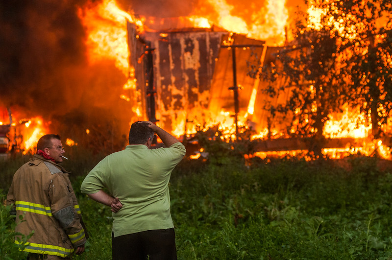A Franklin County firefighter looks on as Danny Garrison watches his barn go up in flames after being struck by lightning in Frankfort, Kentucky.