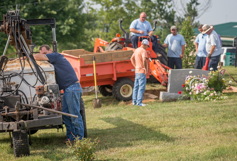 Danny Monroe stands with his mother's casket after it was exhumed so her grave could be dug deeper at the Frankfort Cemetery, one day after it was originally buried in Frankfort, Kentucky.